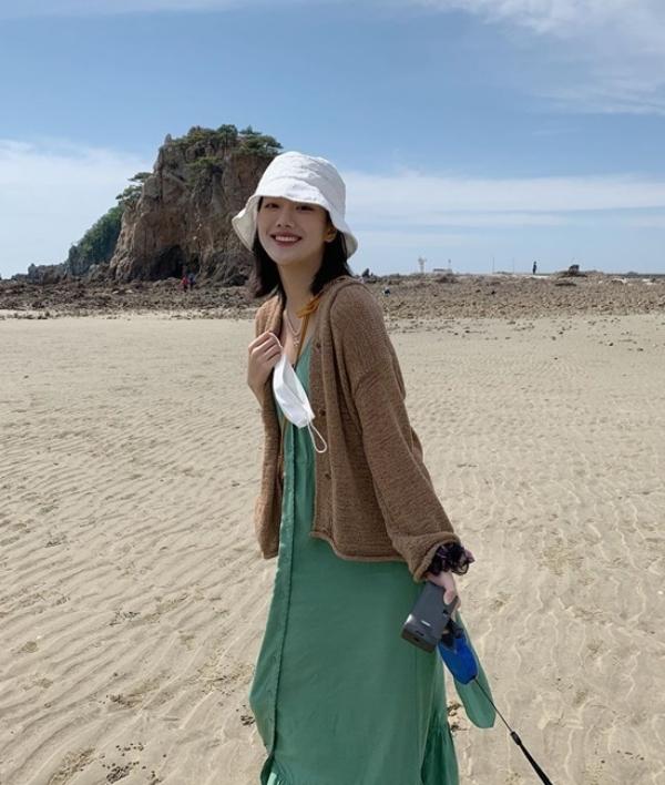 Style đi biển rạng ngời của Naeun là phối váy hai dây chất len tăm với áo cardigan vintage.