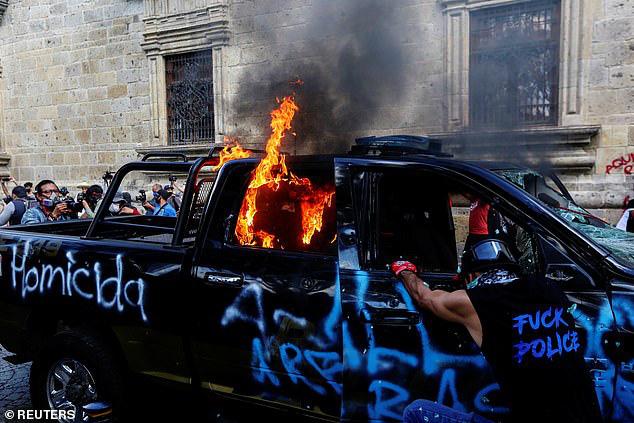 Người biểu tình vẽ bậy và đốt xe cảnh sát.