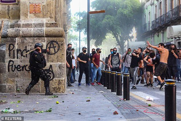 Một sĩ quan cảnh sát đụng độ với những người biểu tình.
