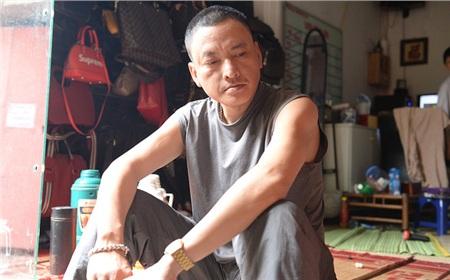 Anh Trần Thụ ngồi buồn rầu, thất thần trước cửa nhà.