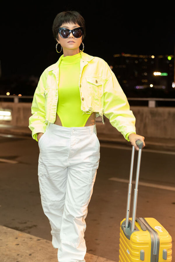 Set đồ thời trang sân bay trẻ trung, năng động của Hoa hậu H'Hen Niê với bodysuit cổ lọ cut - out phần eo mix cùng áo khoác neon xanh sáng lóa phối cùng quần trắng