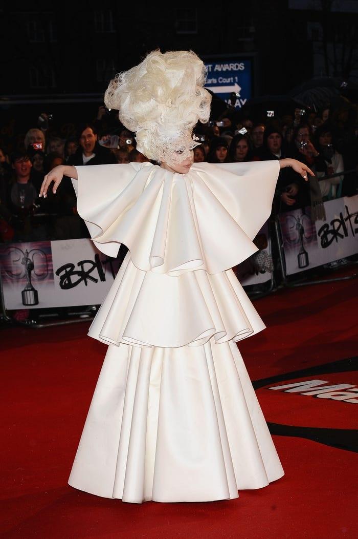 Nữ ca sĩ khoác lên mình bộ tóc giả màu trắng cao ngất và bộ váy trắng xếp tầng trên thảm đỏ lễ trao giải Brit 2010. Đây là một trong những trang phục mang tính biểu tượng nhất của cô cho đến nay.