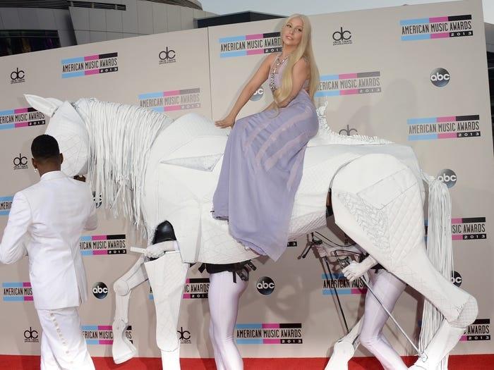 Lại một lần nữa Gaga làm thiên hạ choáng ngợp khi cưỡi ngựa máy lên thảm đỏ American Music Awards 2013. Toàn bộ vẻ ngoài của cô trông giống như một Lady Godiva hiện đại, với mái tóc vàng dài và một chiếc váy dạ hội màu mè.