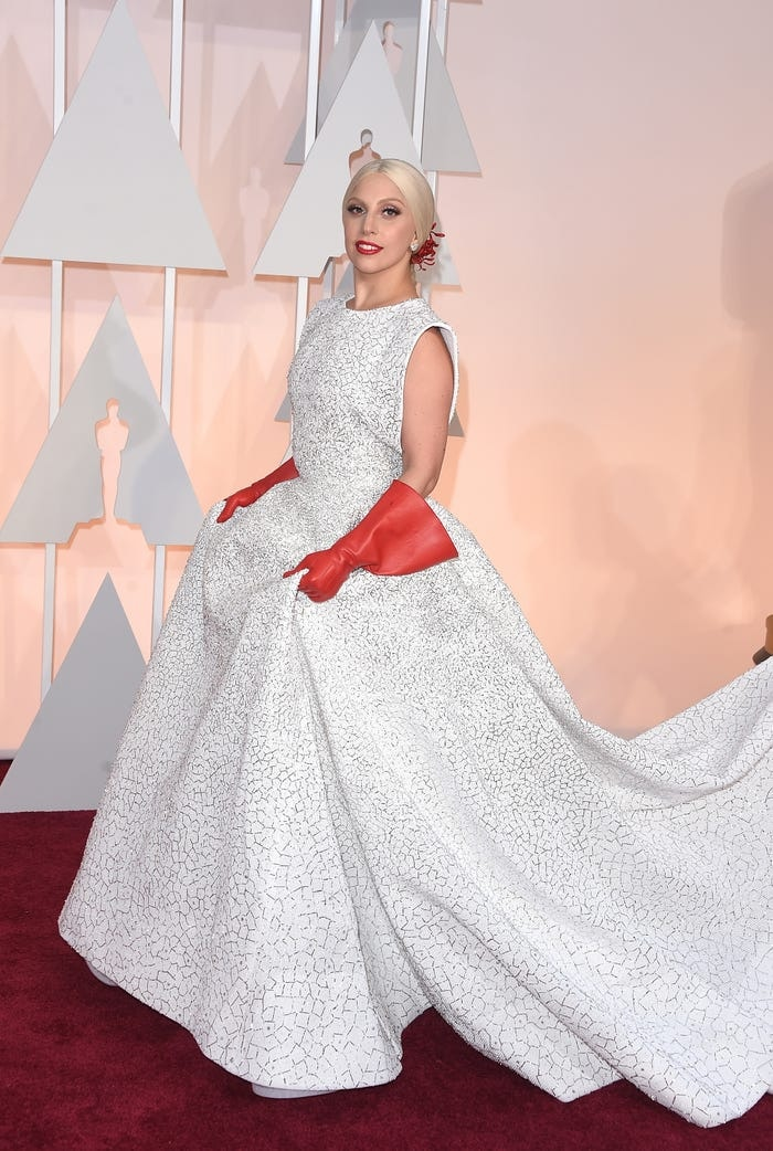 Trong lễ trao giải Oscar lần thứ 87, Gaga mang đến hơi thở những năm 1950 với một chiếc váy đơn sắc đồ sộ. Nữ ca sĩ không quên mang theo găng tay màu đỏ ấn tượng để tô điểm cho màu váy trắng.
