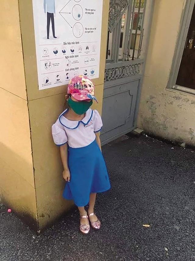 Sợ bị phạt vì đi học sớm, một học sinh Trường Tiểu học Quang Trung (quận Ngô Quyền, TP.Hải Phòng) đã đứng ngoài cổng trường giữa trời nắng. Ảnh: TL