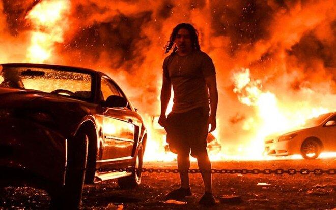 Sau cái chết củaGeorge Floyd, các cuộc biểu tình với khẩu hiệu 'Tôi không thể thở' lan khắp nhiều thành phố Mỹ đòi công lý được thực thi. Trong ảnh, chiếc xe bắt lửa tại một gara trong cuộc biểu tình ở Minneapolis, ngày 29/5.