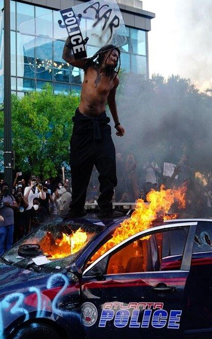 Một người đàn ông đứng trên nóc xe cảnh sát trong một cuộc biểu tình bên ngoài trung tâm CNN tại Georgia.