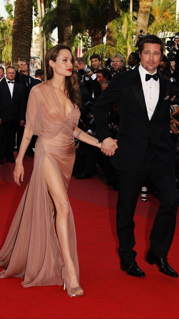 Khoảnh khắc anh chồng Brad Pitt tay trong tay với cô vợ xinh đẹp Jolie sải bước trên thảm đỏ LHP Cannes lần thứ 62. Bộ váy xuyên thấu trong suốt màu hồng pastel khoe được cơ thể đẹp tuyệt mỹ của Angelina với vòng 1 căng đầy và đôi chân dài miên man