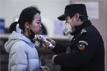 Một người dân Trung Quốc đang được kiểm tra nhiệt độ cơ thể.