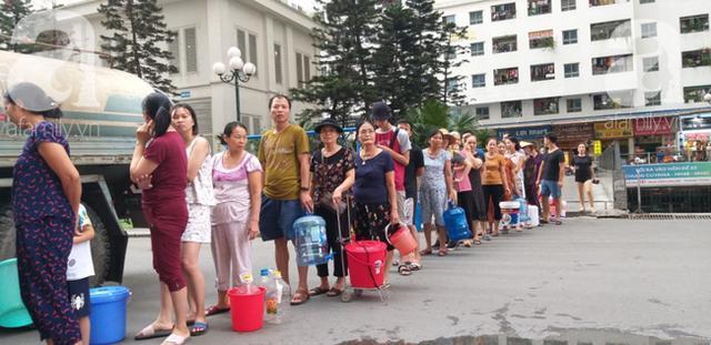 Người dân xếp hàng đứng chờ từng chai nước sạch.