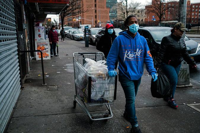 Một người đàn ông giao hàng tạp hóa cho một gia đình ở khu vực Bronx.