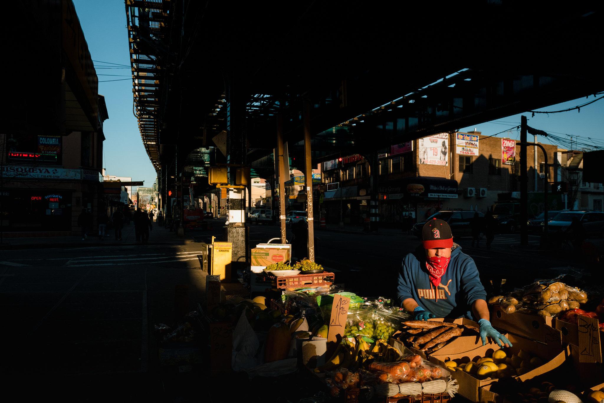 Một người bán trái cây ở Jackson Heights. Người bán hàng rong, nhân viên giao hàng, người đưa thư, người thu gom rác, thu ngân ở quầy thực phẩm - số ít những người vẫn phải tiếp tục đi làm được coi là nhịp đập hiếm hoi của cuộc sống bình thường còn xuất hiện trong thành phố.