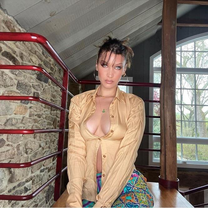 Chỉ với cái áo sơ mi nhăn nhúm màu be, bung hết cả nút chỉ chừa lại một cúc áo ngay ngực, Bella Hadid makeup trang điểm pose dáng khi đang ở nhà