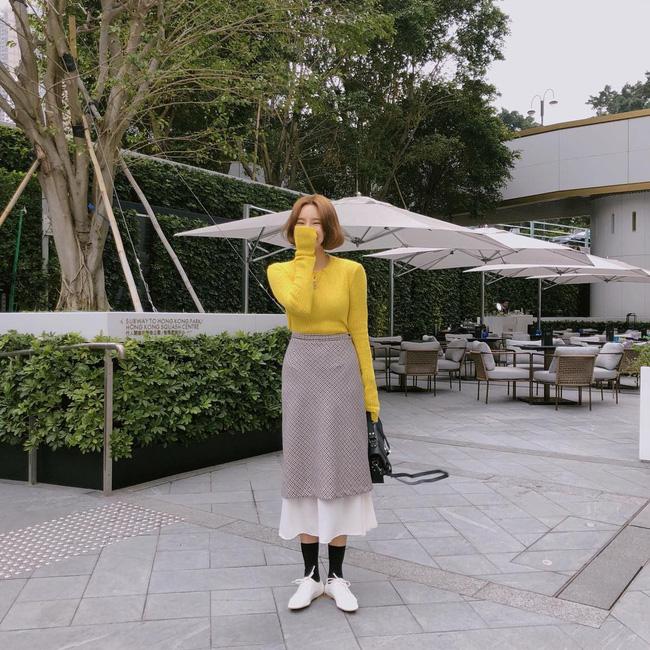 Cô nàng này có cách mix đồ khá hay ho, áo len tone màu vàng nổi bật được kết hợp đầy ấn tượng cùng chân váy midi xếp tầng và giày oxford.