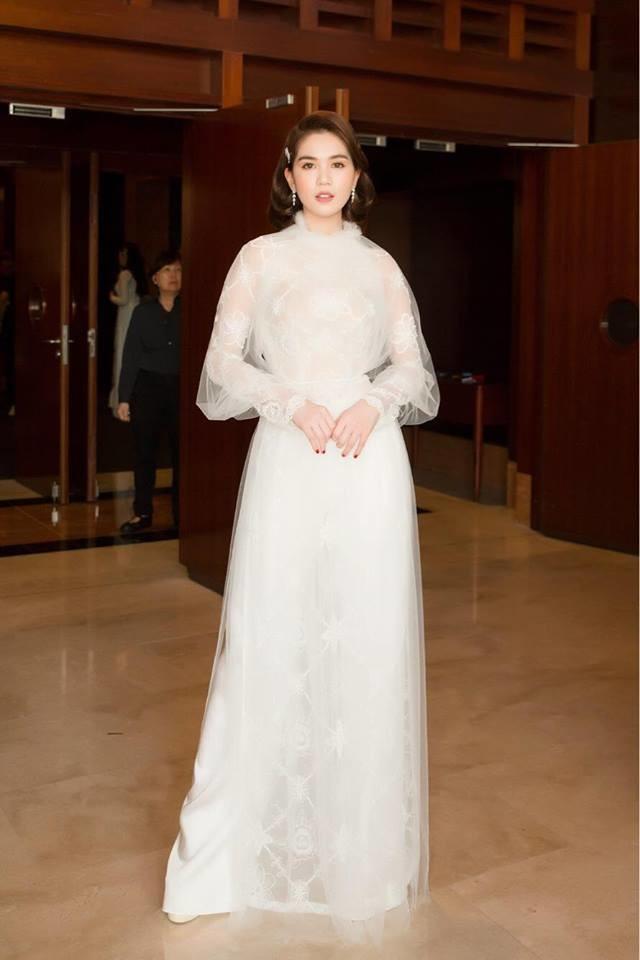 Khi chuyển sang tóc ngắn hiện đại sang trọng, Ngọc Trinh cũng thay đổi phong cách với những tà áo dài các tân đương thời. Thiết kế áo dài trắng kiểu dáng phảng phất nét hoàng gia với vai phồng vay phủ voan trắng yêu kiều.