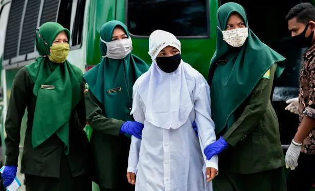 Cảnh sát đưa người phụ nữ tới nơi thực hiện hình phạt.