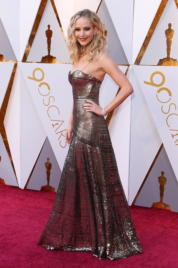 Jennifer Lawrence tỏa sáng trong chiếc váy metalic của Dior. Nữ diễn viên gây ấn tượng với kiểu tóc và trang điểm hút hồn. Được biết, người 'tạo' nên gương mặt xinh đẹp của JLaw tối nay là chuyên gia trang điểm gốc Việt Hung Van Ngo.