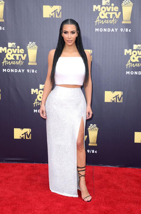 Kim Kardashian xuất hiện trong bộ cánh trắng lung linh của nhãn hàng Versace. Nữ diễn viên một lần nữa để mái tóc bện đặc trưng của những cô gái châu Phi. Trước đây, Kim từng bị 'ném đá' tơi bời bởi người hâm mộ cho rằng mái tóc này đối với Kim là 'lệch lạc văn hoá'.