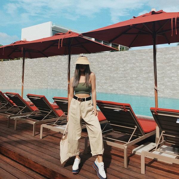 Châu Bùi lựa chọn kiểu áo quây không tay. Cô nàng 9x kết hợp item này cùng với quần kaki ống loe. Để diện mạo thêm phần cá tính thời thượng, cô khéo léo nhấn nhá thêm cho trang phục các phụkiện như giày đế độn, túi tote, mũ cói và thắt lưng da của Gucci.