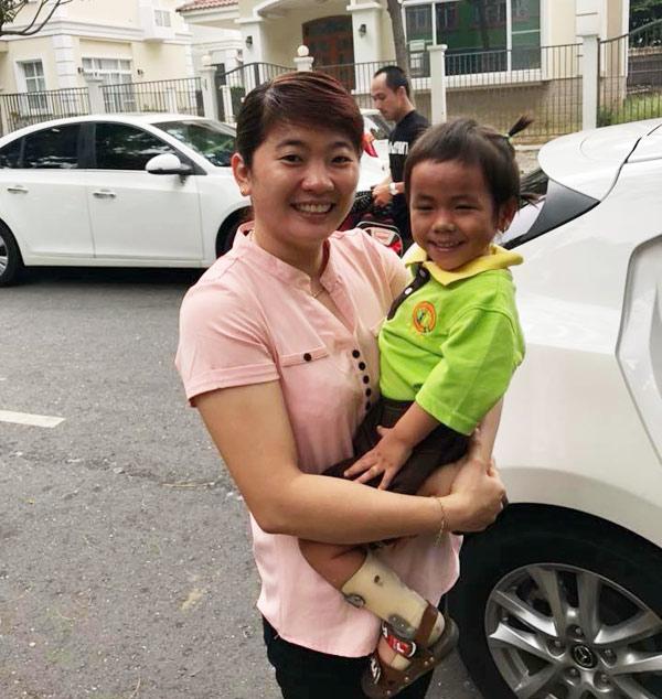 Cô bé cười tươi khi được cô giáo đón vào lớp trong ngày đầu đến trường