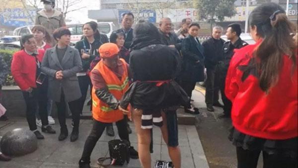 Hành động của người phụ nữ thu hút rất đông người đi đường đứng lại xem