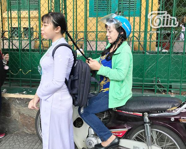 Người mẹ ngồi trên xe máy thắt bím cho con gái trước cổng trường.