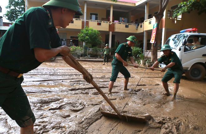 Lực lượng chức năng giúp nạo vét bùn ở các công sở, trường học sau lũ.