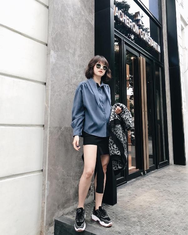 Tâm Xíu phá cách khi lựa chọn áo sơ mi tay bồng kết hợp cùng chân váy cách điệu và giày sneaker.