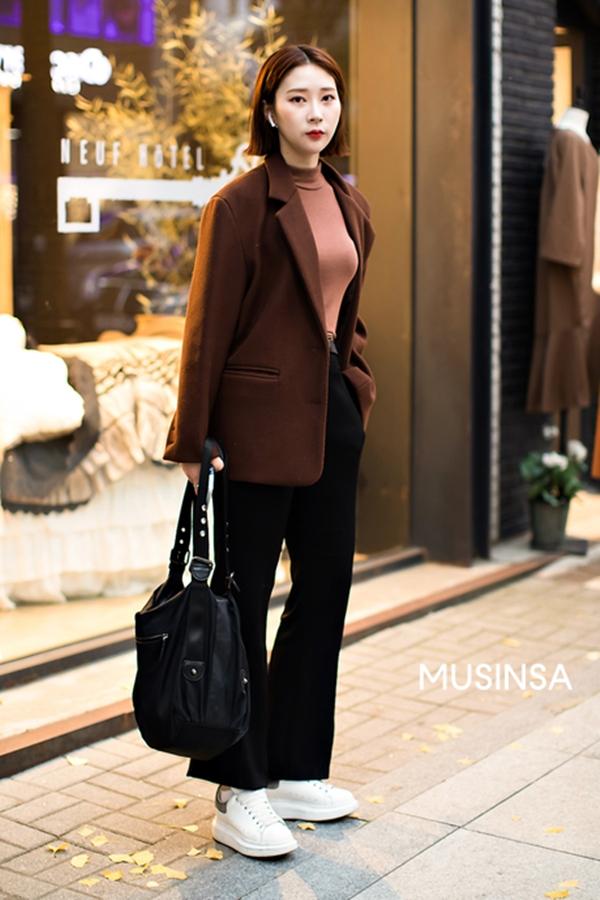 Hòa mình vào xu hướng diện đồ với tông màu mang nét đặc trưng của mùa lạnh, cô bạn này lựa chọn áo thun mix cùng blazer màu nâu đất và quần vải ống loe, tạo nên set đồ vừa trẻ trung vừa thanh lịch.