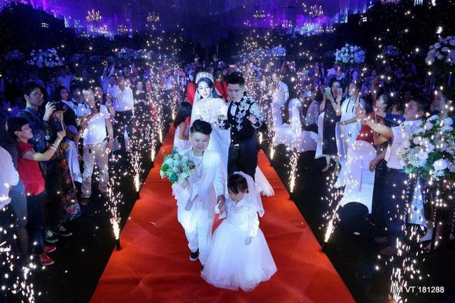 Hai con Hoàng Anh và Trâm Anh hạnh phúc cầm hoa tươi dẫn bố mẹ tiến vào lễ đường
