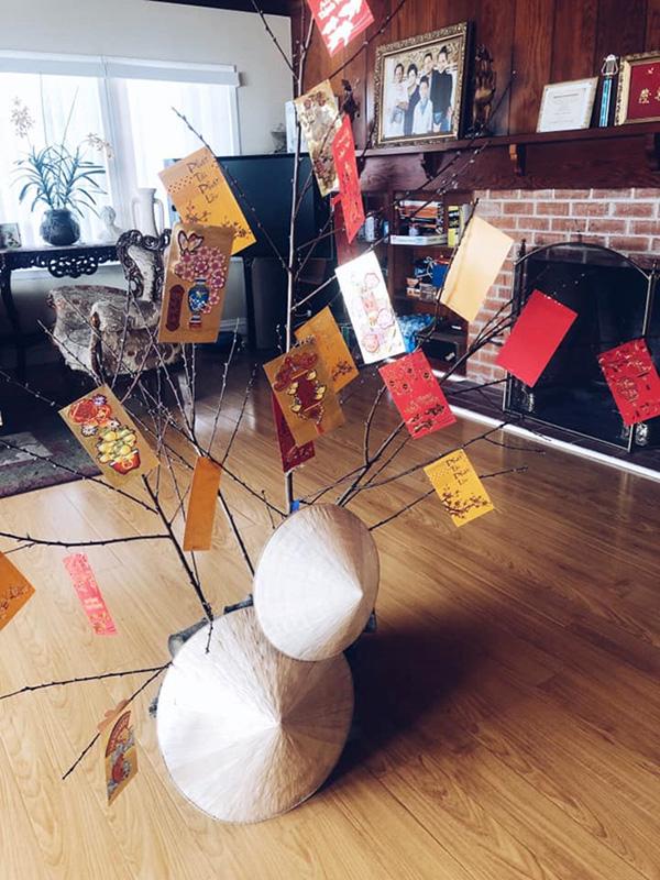 Kim Hiền trang trí phòng khách bằng cây tầm xuân, nón lá và những phong bao lì xì màu đỏ.