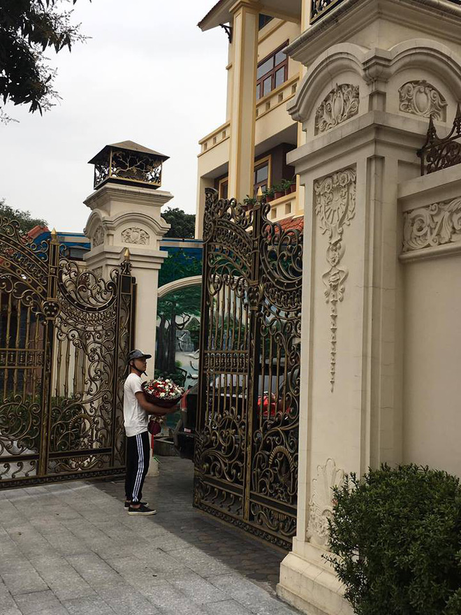 Anh chàng ôm hoa đợi để tặng trước cổng nhà.