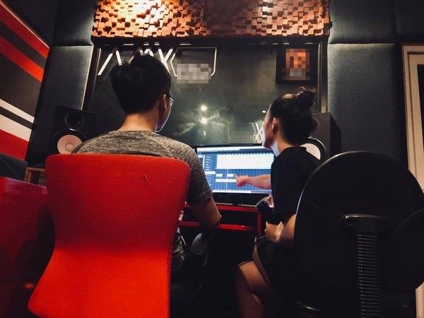 Bức ảnh chụp lại khoảnh khắc cô nàng đang ngồi trong phòng thu, thảo luận về một đoạn nhạc nào đó (dựa trên màn hình của máy tính) với người bạn này.