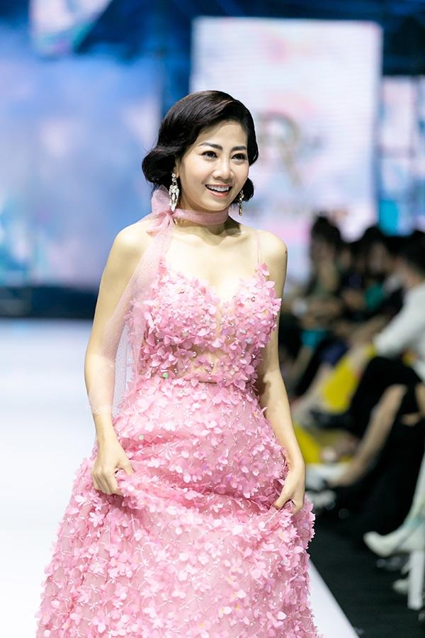 Mở màn cho BST 'Endless Summer' là diễn viên Mai Phương. Trong màn sương khói ảo dịu, âm thanh trong trẻo, Mai Phương khoác lên mình mẫu đầm công chúa tông hồng ngọt ngào được kết thủ công hàng trăm cánh hoa lấp lánh.