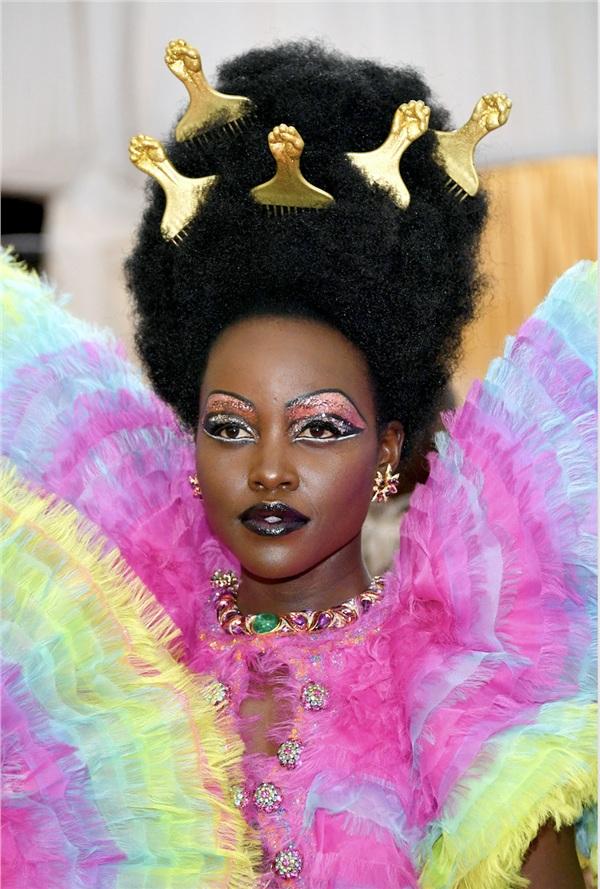 Lấy cảm hứng từ nhân vật DragQueen Divine, nữ diễn viênLupita Nyong'o vừa xuất hiện đã gây sự chú ý với bộ cánh 'lòe xòe' 7 sắc cầu vồng cùng đôi mắt, đôi môi lấp lánh cũng nhiều màu không kém.