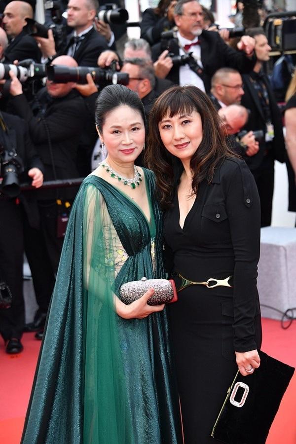 Một phụ nữ lớn tuổi diện chiếc đầm xanh cùng trang sức ton-sur-ton nhưng không nhận được sự chú ý khi xuất hiện tại thảm đỏ