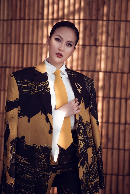 Bộ vest họa tiết màu vàng - đen mạnh mẽ, ấn tượngkết hợp với sơ mi trắng, cà vạt màu vàng giúp Khánh Ngân trở nên nổi bật, đầy thu hút.