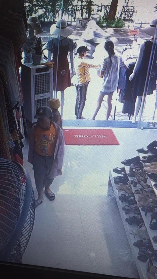 Người mẹ đứng ngoài vờ xem quần áo để đánh lạc hướng còn đứa con trai lẻn vào shop quần áo.