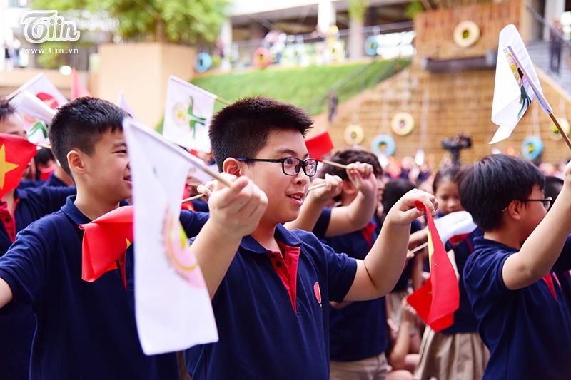 Không thả bóng bay, học sinh trường Marie Curie cầm cờ đỏ sao vàng và cờ mang thông điệp bảo vệ môi trường.