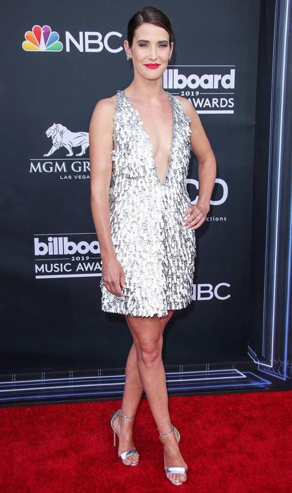 Thiết kế váy ánh kim xẻ cổ sâu ánh kim được Cobie Smulders lựa chọn. Cô phối đơn giản cùng giày cao gót màu bạc và tóc búi gọn.
