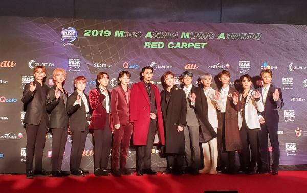 Seventeen chọn tông đỏ - đen làm chủ đạo. Vị trí center - Kim Mingyu được nhiều fan nhận xét chẳng khác gì 'tổng tài' với chiếc áo coat dài màu đỏ quyền lực.