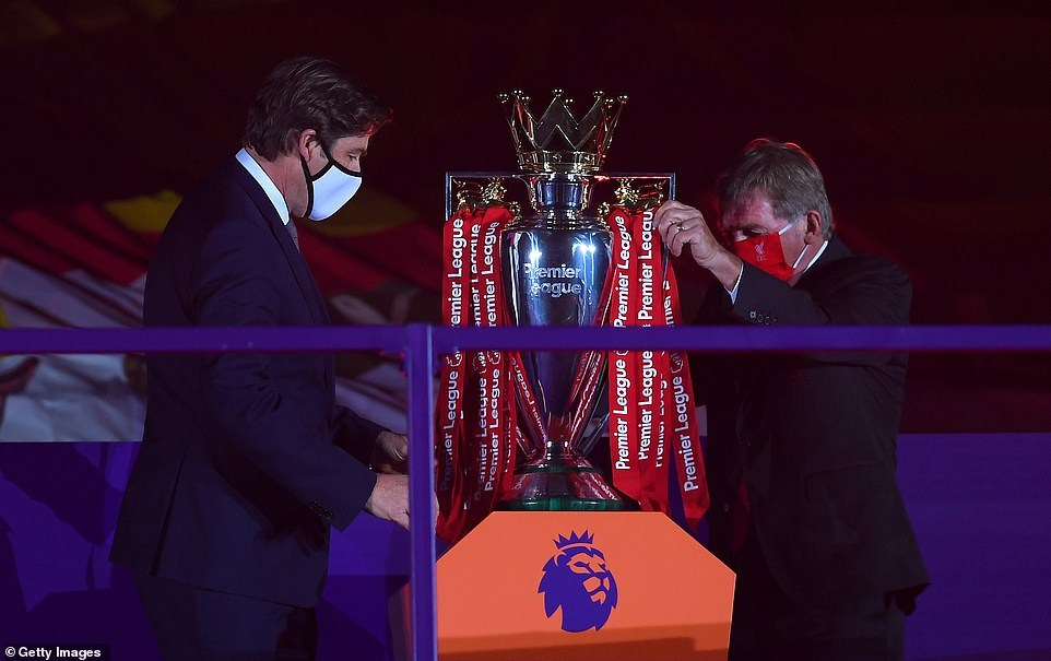 HLV huyền thoại của Liverpool Kenny Dalglish và đại diện giải Ngoại hạng Anh đưa cúp vô địch lên bục nhận giải. Ảnh: Getty