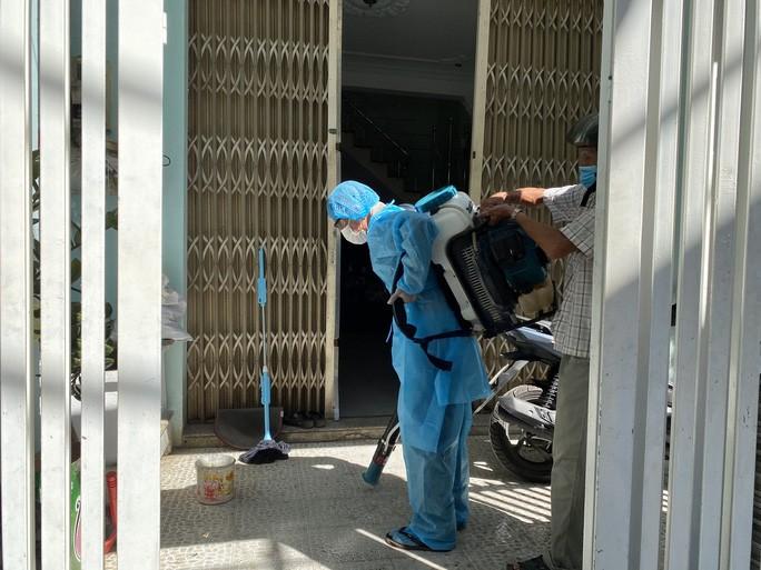 Cán bộ y tế phun hóa chất khử khuẩn tại nhà bên cạnh của bệnh nhân 418 sáng 26-7