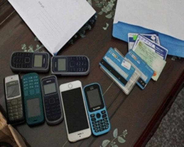 Hai đối tượng sử dụng mạng xã hội và điện thoại để lừa đảo bị bắt giữ cùng tang vật.