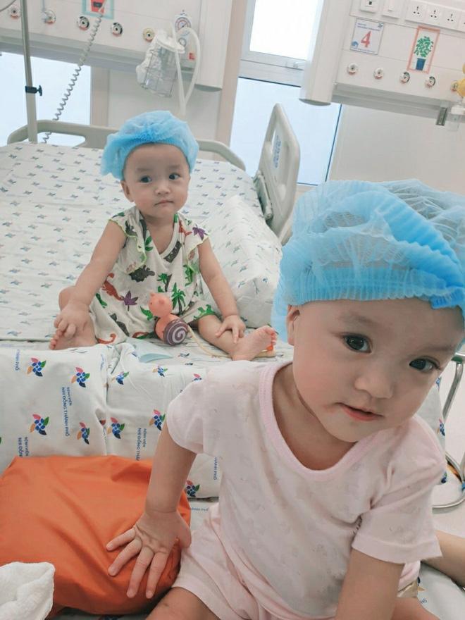 Hai chị em khỏe mạnh, cười đùa khi được bố mẹ và các bác sĩ đến thăm