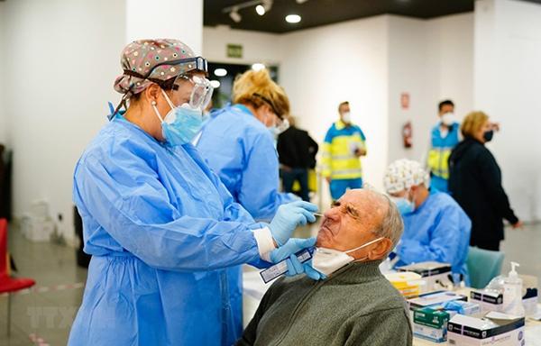 Nhân viên y tế lấy mẫu xét nghiệm cho người dân tại thủ đô Madrid. (Ảnh: AFP)