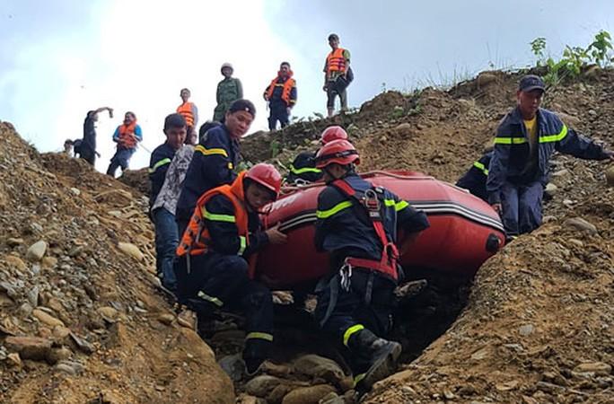 Lực lượng tìm kiếm khiêng canô vượt đập thủy điện Rào Trăng 4 để ngược dòng tìm kiếm những người mất tích ở Rào Trăng 3 Ảnh: NHẬT LUẬT