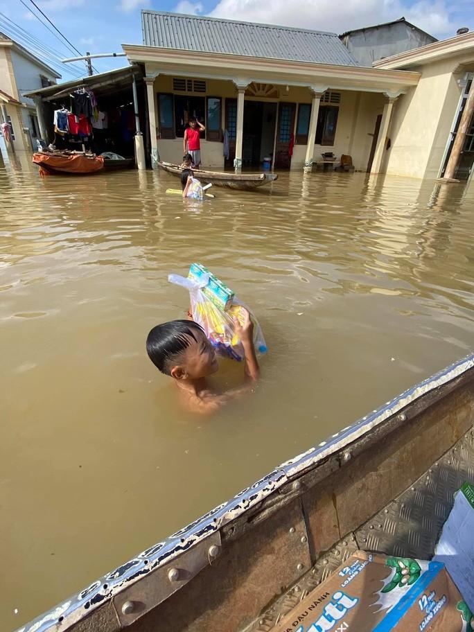 Một cháu bé vui mừng bơi ra xuồng cứu trợ để nhận thực phẩm