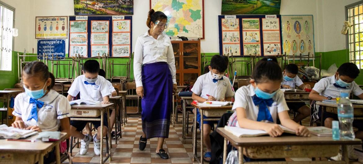 Giáo viên và học sinh đeo khẩu trang và giữ khoảng cách vật lý tại một trường học ở Campuchia. (Ảnh: UN)