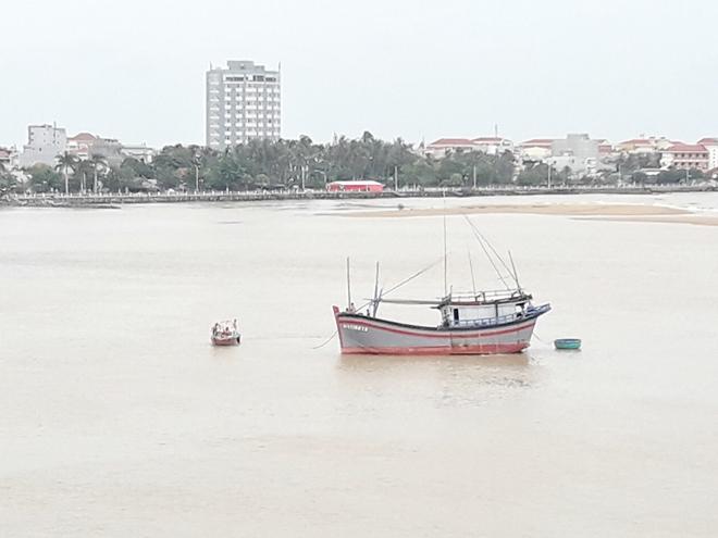 Trong lúc vào sông Chùa để neo đậu tránh bão, một tàu cá bị mắc cạn ở hạ lưu sông Đà Rằng sáng nay (27-10) đang được Bộ đội biên phòng Phú Yên kiểm tra để giải cứu. Ảnh: Hữu Toàn
